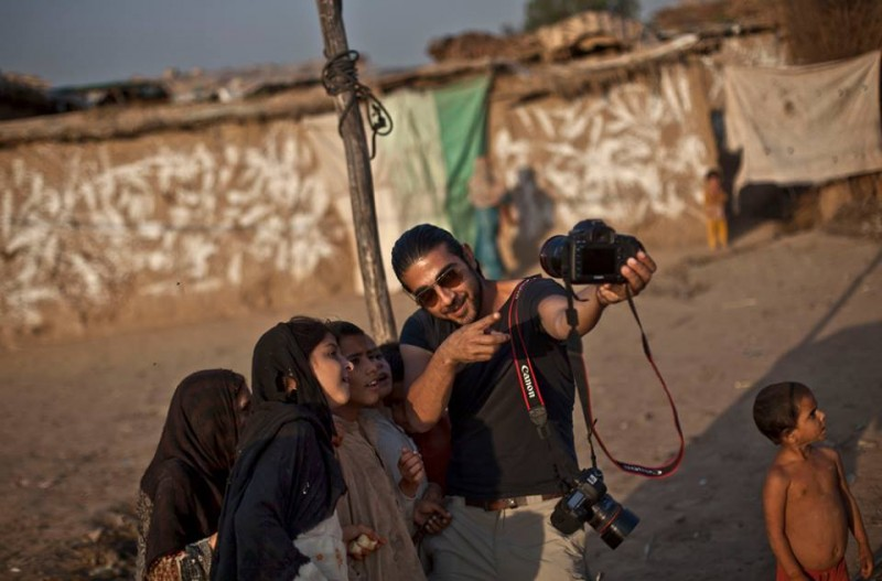 Le photographe Muhammed Muheisen montre à ces enfants réfugiés afghans comment fonctionne un appareil photo dans un quartier d'Islamabad, Pakistan, lundi 21 octobre 2013. Photo AP Photo/Nathalie Bardou