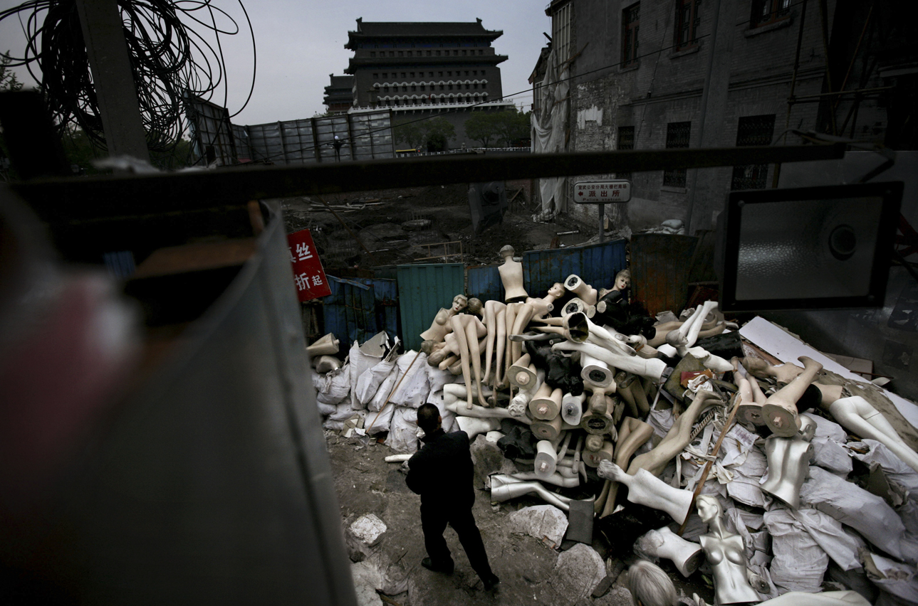 A Chinese man walks by mannequins amongst the rubble of demolished shops in Beijing Saturday, May 3, 2008. Large swathes of the city are being demolished, to be replaced by modern commercial and residential complexes as the city modernizes in preparation for the 2008 Olympic Games.(AP Photo/Oded Balilty)