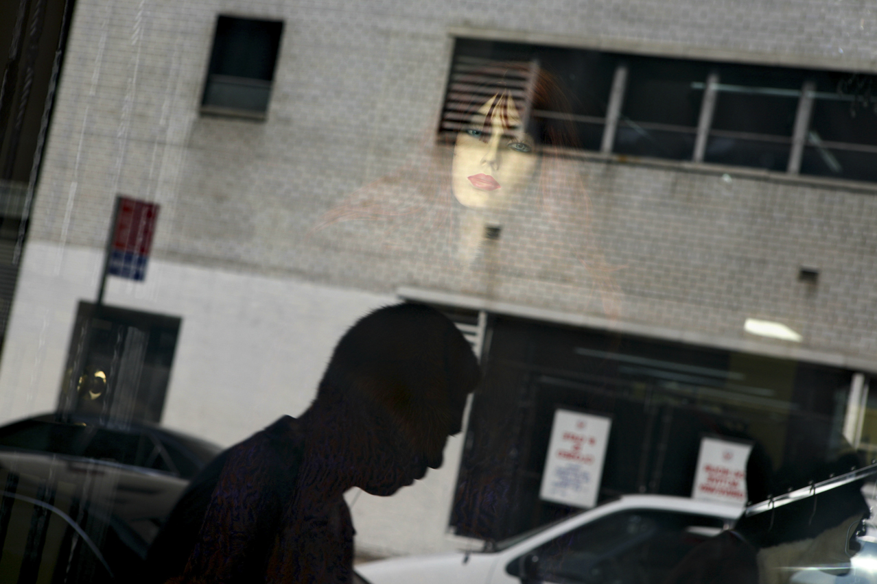 Mannequins and pedestrians are reflected in a clothing store window at the Fashion district during the Fashion Week in New York, Thursday, Sept. 6, 2007. (AP Photo/Oded Balilty)