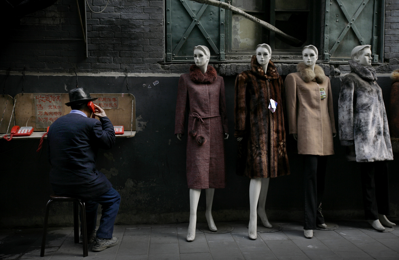 A man speaks on phone next to a clothing shop at a market in Beijing, Wednesday, Dec. 26, 2007.(AP Photo/Oded Balilty)