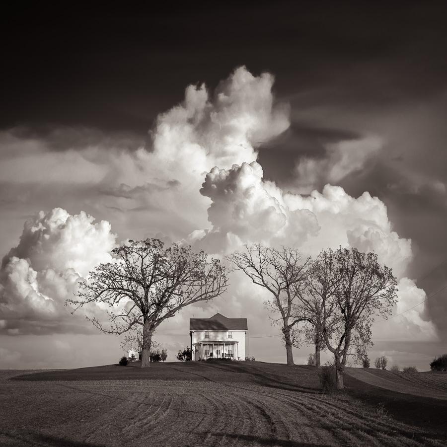 Maison dans le Midwest américain, dans un champ avec un ciel chargé de nuage, photo monochrome, noir et blanc