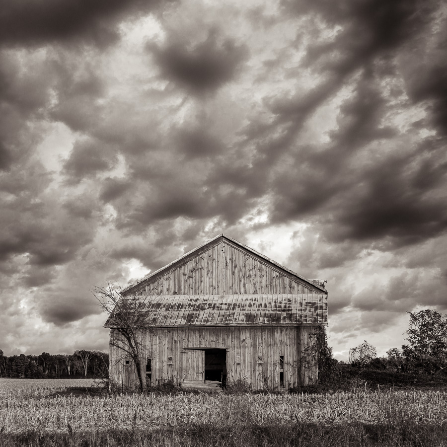 Grange en bois dans un champ du Midwest américain avant une tempête, ciel sombre et chargé, paysage monochrome