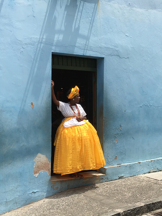 "Alexandre Weber Switzerland 1st Place, Photographer of the Year Baiana in yellow and blue ""The picture was taken in Salvador de Bahia, Brazil, spontaneously, after a truck drove by. The woman with traditional clothes of a ""baiana"", was looking after the truck, during her work break."" Location: Salvador de Bahia, Brazil Shot on iPhone 6S"