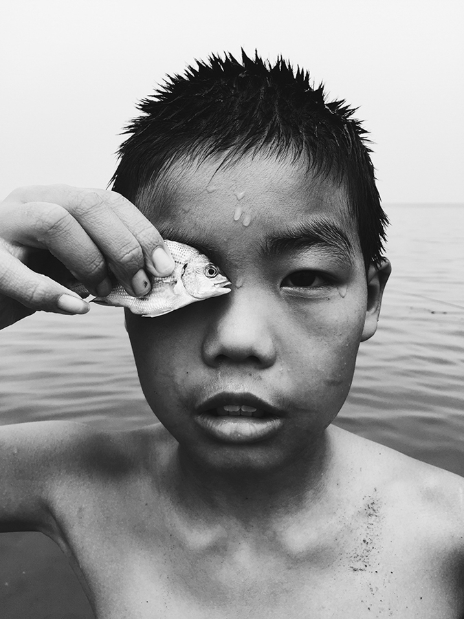 "Huapeng Zhao China 2nd Place, Photographer of the Year Eye to eye ""I met this boy while walking at the seaside. When I was trying to take a picture of him, he put the fish he caught in front of his eye."" Location: YanTai ShanDong province, China Shot on iPhone 6"