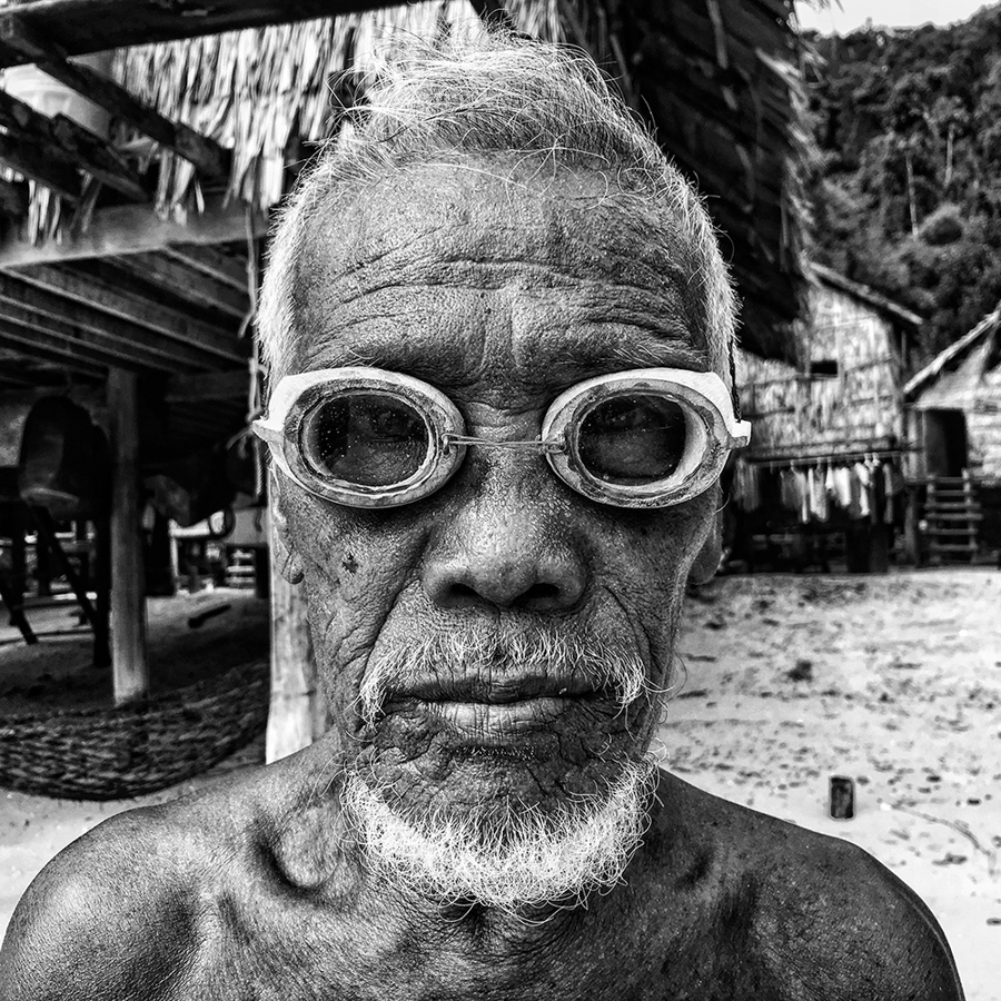 "Scott Woodward Singapore 1st Place – Portrait Salamah ""Moken village elder, Salamah, wearing his hand- carved wooden dive goggles on the beach at Au Bon Yai, a tiny island community of about 300 sea gypsies off the coast of Phang Nga, Thailand."" Location: Ko Surin, Thailand Shot on iPhone 6S"